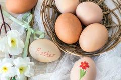 """L'uovo di Hen's con il  del """"Easter†del testo e il ` s della gallina eggs in canestro di vimini ed in salice con il fiore  Immagini Stock"""