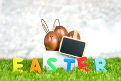 L'uovo di Pasqua dell'oro di Rosa in scatola bianca di legno e la lavagna in bianco tagliano Immagini Stock Libere da Diritti