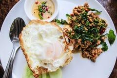 L'uovo fritto ha completato con carne di maiale in padella e basilico fotografie stock