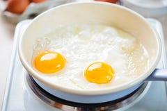 L'uovo ha fritto su olio vegetale sulla pentola blu Fotografie Stock