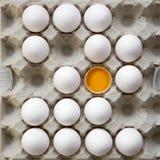 L'uovo incrinato tra altro pollo eggs in scatola delle uova del cartone, vista sopraelevata Da sopra, vista superiore immagini stock libere da diritti