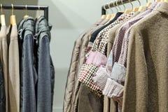 L'usage d'hommes différent (vestes, chemises, chandails) sur les cintres en bois Images stock