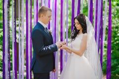 L'usage de jeunes mariés à une cérémonie de mariage quand anneaux sur un fond des rubans multicolores, amour, mariage, rel Photos stock