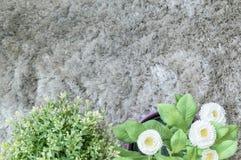 L'usine artificielle de plan rapproché avec la fleur blanche dans le pot sur le tapis gris brouillé a donné au fond une consistan Photo libre de droits