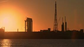 L'usine et le raffinerie de pétrole pendant la lentille de coucher du soleil évasent clips vidéos