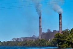 L'usine pollue l'environnement Pollution environnementale d'usine de nature Une usine avec des tuyaux de tabagisme près de l'eau  photographie stock libre de droits