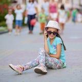 L'uso alla moda del bambino della bambina jeans copre ed occhiali da sole Fotografia Stock