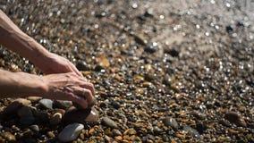 L'uso dell'uomo la sua mano che mette in bacino le pietre sulla costa Immagine Stock Libera da Diritti