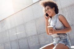 L'uso della giovane donna complessivo mette nella via della città che si siede con la tazza di caffè che parla sullo smartphone a immagine stock
