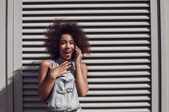 L'uso della giovane donna complessivo mette sull'otturatore che ha conversazione sullo smartphone impressionato fotografia stock libera da diritti