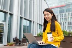 L'uso della giovane donna del computer portatile e gode del caffè Fotografie Stock Libere da Diritti