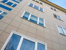 Rifinitura della facciata di nuovo condominio con le piastrelle di