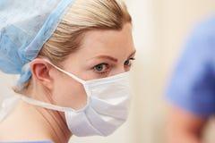 L'uso di In Operating Theatre dell'infermiere sfrega e maschera Immagine Stock
