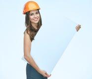 L'uso sorridente della donna protegge il casco del costruttore che tiene il banne bianco Fotografie Stock