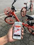 """L'utilisateur emploie l'application sur l'iPhone pour la bicyclette de location de  d'""""mobike†Photos stock"""