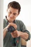 L'utilisation de jeune homme électrique forent dedans le projet de rénovation de Chambre Photographie stock libre de droits