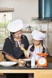 L'utilisation de mère et de fille battent pour mélanger la farine d'oeufs et de blé Image libre de droits