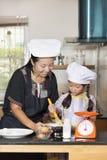 L'utilisation de mère et de fille battent pour mélanger la farine d'oeufs et de blé Photos libres de droits