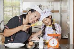 L'utilisation de mère et de fille battent pour mélanger la farine d'oeufs et de blé Photographie stock