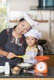 L'utilisation de mère et de fille battent pour mélanger la farine d'oeufs et de blé Images libres de droits