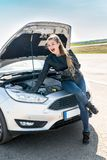 L woman driver with wrenches sitting on broken car stock photos