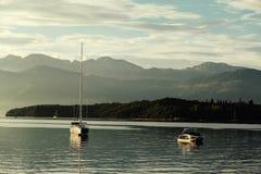 L'yacht ed il battello da diporto al tramonto con le montagne in Cattaro abbaiano, m. Immagine Stock