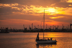 L'yacht naviga nel porto di Varna al tramonto Fotografie Stock Libere da Diritti