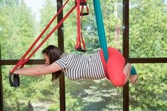 L'yoga aerea della giovane donna incinta esercita l'yoga dell'interno della mosca fotografia stock