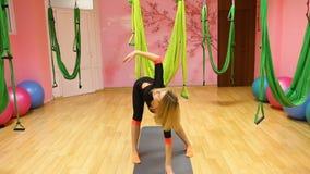 L'yoga antigravità, donna atletica che fa l'yoga esercita dell'interno video d archivio