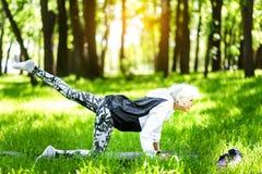 L'yoga concentrata di addestramento della donna anziana si esercita in parco Fotografia Stock
