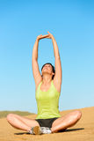 L'yoga della donna e si rilassa sulla spiaggia Immagini Stock