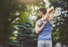 L'yoga di addestramento dell'uomo in testa della mucca posa all'aperto Fotografia Stock