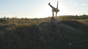 L'yoga di pratica del tipo caucasico si muove e posiziona in natura Giovane uomo sportivo che sta alla posa di yoga all'aperto at Fotografia Stock