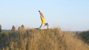 L'yoga di pratica del tipo caucasico si muove e posiziona in natura Giovane uomo sportivo che sta alla posa di yoga all'aperto at Immagine Stock Libera da Diritti