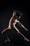 L'yoga di pratica dell'uomo bello nello scuro ha acceso lo studio Fotografia Stock Libera da Diritti