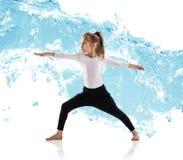 L'yoga di pratica della bambina in acqua spruzza Fotografia Stock