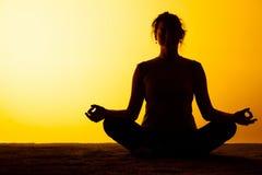 L'yoga di pratica della donna alla luce di tramonto Immagine Stock