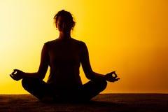 L'yoga di pratica della donna alla luce di tramonto Fotografia Stock Libera da Diritti