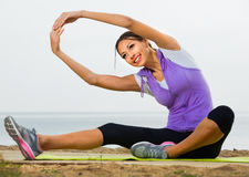 L'yoga di pratica della donna posa la seduta sulla spiaggia dal mare Immagine Stock Libera da Diritti