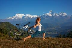 L'yoga di pratica della donna, rilassantesi dopo la guida bikes su in supporto Fotografia Stock Libera da Diritti