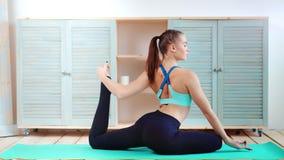 L'yoga di pratica della giovane donna attraente che fa il piccione posa a casa la vista laterale del fondo archivi video