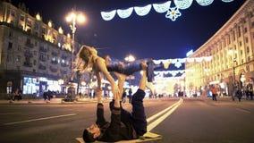 L'yoga di pratica sorridente di acro delle coppie sportive posa sulla via, hobby estremo archivi video