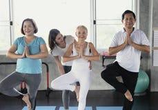 L'yoga di Young Female Performing dell'istruttore insegna ad anziani alla classe anziana di sport fotografie stock