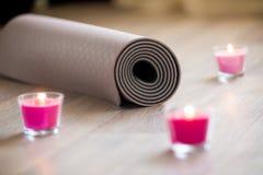 L'yoga marrone piegata, stuoia dei pilates sul pavimento con acceso è aumentato Ca Fotografia Stock