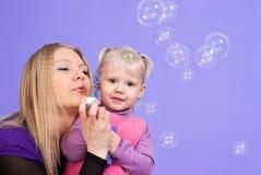l5At den caucasian dottern för bubblor henne modern Arkivfoton