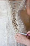 Laçage d'une robe de mariage Photographie stock