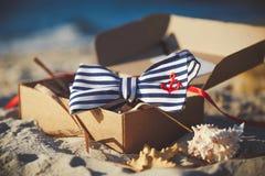 Laço à moda na caixa do ofício na areia ` S dos homens e acessórios do ` s das mulheres no fundo do Sandy Beach fotografia de stock royalty free