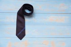 Laço azul e preto listrado do pescoço no fundo de madeira pastel azul com espaço da cópia Conceito do dia do pai imagens de stock royalty free