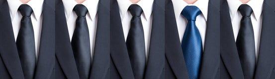 Laço azul entre gravatas pretas Fotografia de Stock Royalty Free