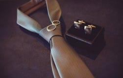 Laço do casamento, alianças de casamento do ouro e botão de punho, cor acolhedor escura Imagem de Stock